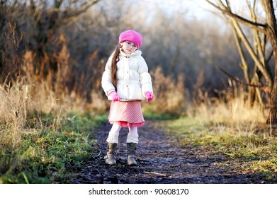 Little child girl in glasses wearing pink cap walks along the forest road