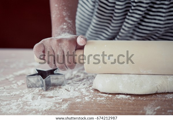 Little child girl hands kneading dough prepare for baking cookies in vintage color tone