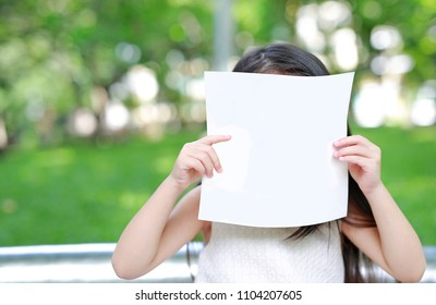 Little child girl hiding face behind blank white paper in the green garden.