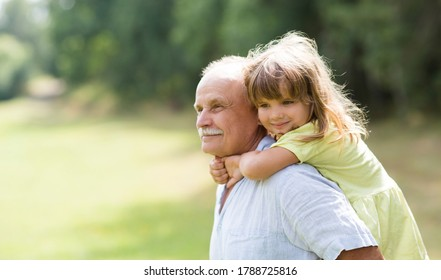 Little child girl hugs grandpa On Walk in the summer outdoors. Concept of friendly family.