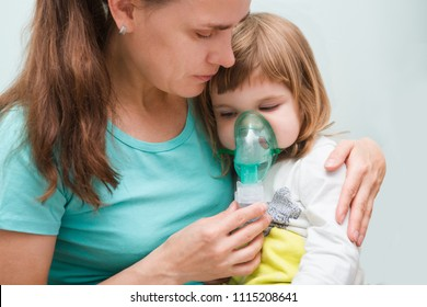 Little child girl inhaling from the inhaler with nebulizer at home. A child  with respiratory disease  in a mask for inhalations sits on hands at the mother. Asthma patient
