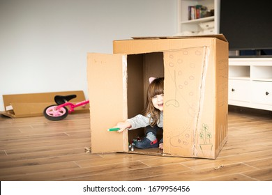 Little child girl looking out of a cardboard playhouse while moving in a new house. Lockdown activity idea.