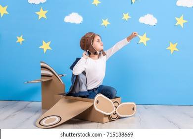 Little child girl in a pilot's costume is playing and dreaming of flying over the clouds.