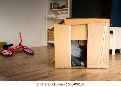 Little child girl playing in a cardboard playhouse while moving in a new house.