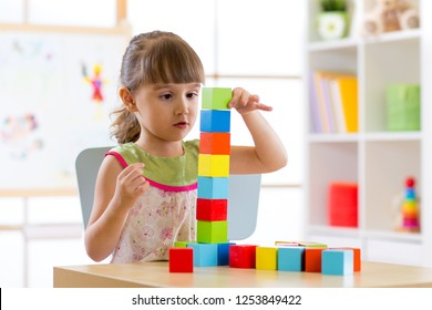 Little child girl playing colorful wood blocks