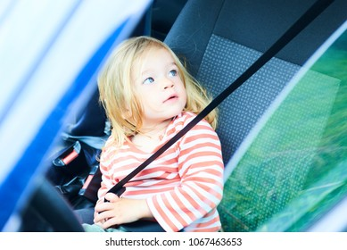 Little child girl playing inside car with seat belt and sitting on front driver seat during a break on a family vacation road trip. Traveling by car with kids.