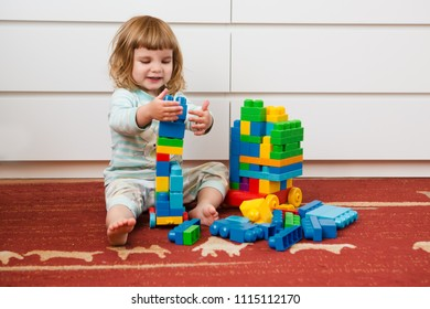 Little child girl playing with lots of colorful plastic blocks constructor sitting on a floor indoor.