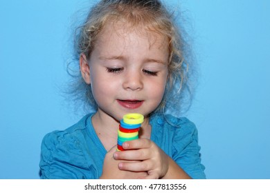 Little child girl playing with sorter toys on the blue background close-up
