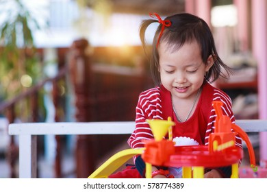 little child girl  playing with toys at  home.