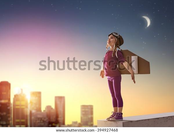 Niña pequeña juega al astronauta. Niño en el fondo del cielo atardecer. Niño vestido con un traje astronauta toca y sueña con convertirse en un hombre espacial.