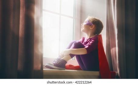 Little child girl plays superhero. Child sitting on the window. Girl power concept.