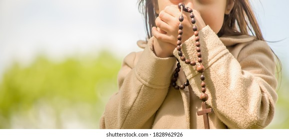 Little child girl praying with wooden rosary. Horizontal image.