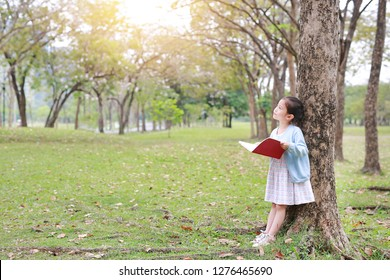 Little child girl reading book in summer park outdoor standing lean against tree trunk with looking to sky.