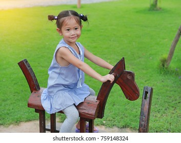Little child girl riding on a wooden toy horse in the green grass garden.