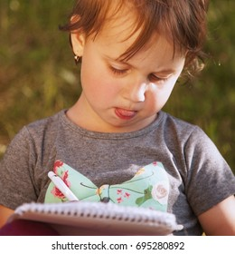 Little child girl sitting on grass and making notes in her notebook. The girl working, studying, learning, keeping a diary. Lifestyle, childhood, nature success concept.