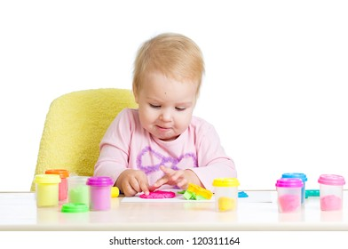Little child girl sitting at table playing with colorful clay