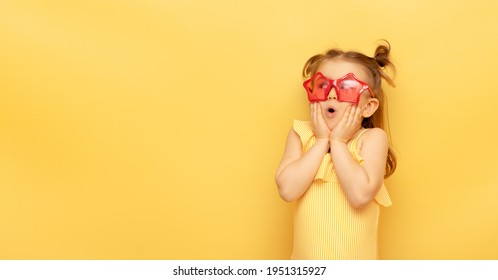 Little child girl in striped swimsuit and red funny summer sunglasses surprised expression looks at camera posing on yellow background, studio portrait.Advertising of children's products and sale