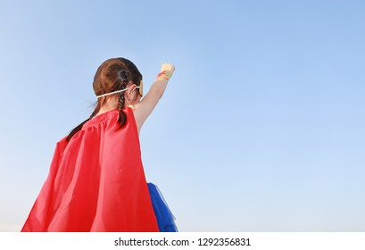Little child girl Superhero in a gesture to fly on clear blue sky background. Kid super hero concept.
