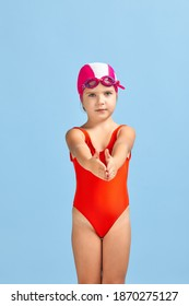 little child girl in swimsuit, swimming goggles and swim cap on blue background. child dreams of becoming a swimming champion