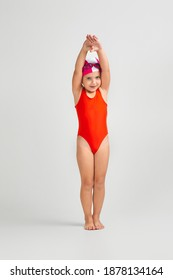 little child girl in swimsuit, swimming goggles and swim cap is preparing for swimmin. Full length. child dreams of becoming a swimming champion