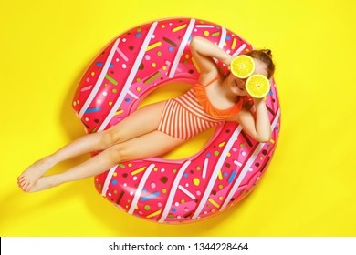A little child girl in a swimwear suit lying on a donut inflatable circle. Yellow background. Top view. Summer concept.