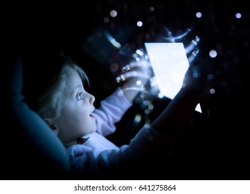 little child girl using tablet technology in bed by night at home. surprised kid daughter in bedroom watching movie or reading or playing game. real people candid dark dreamy shot with flares lights