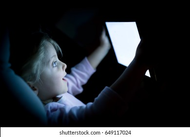little child girl using tablet technology in bed by night at home. Happy surprised kid daughter in bedroom watching movie or reading or playing game. real people candid dark dreamy shot