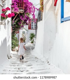 Little child girl in white dress walking the narrow alley with beautiful pink flowers between whitewashed buildings, Greece