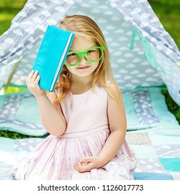 Little child in glasses. The girl has a book. Square. The concept of learning, childhood and lifestyle.
