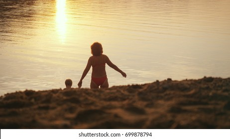little child and grandmom going to the sea holding hands during beautiful sunset happy vacation time