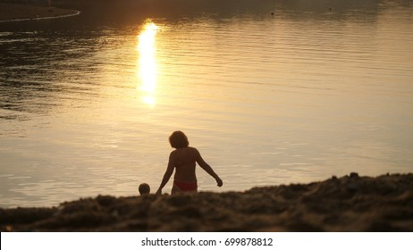 Little child and grandmom going to the sea during beautiful sunset on happy vacation time