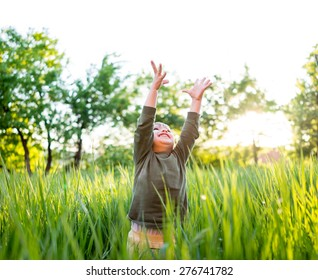 Little child in grass with hands up