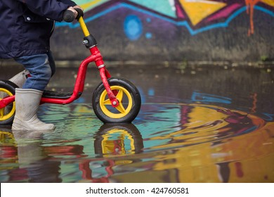 Little child in grey rubber boots cycling after rain.Toddler in a pair of grey rubber boots in a big puddle with graffiti wall reflection. Fun outdoors. Boy on the bike on the street.