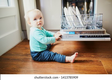 Little child helping to unload dishwasher. Baby girl sitting on the floor in the kitchen. Little child at home