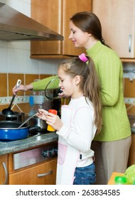 Little child with her mother prepare the soup by the stove in his kitchen. Focus on the child