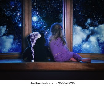 A little child and her teddy bear are looking outside a window with space stars and clouds in the night for a astronomy or dream concept.