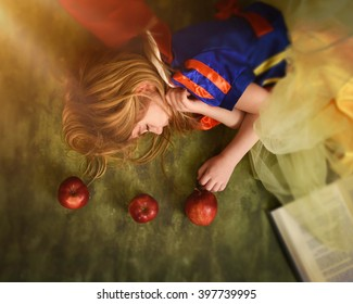 A little child is holding an apple and sleeping with a story book in the forest for a magical fairy tale concept.