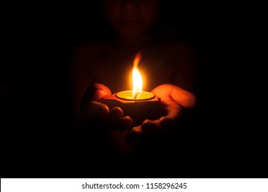 Little child holding burning candle in darkness with noise and grain effect.