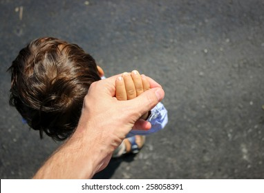 Little Child Holding His Fathers Hand Tightly On The Side Of The Road. Dads Perspective.