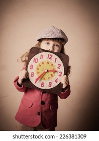 little child holding old clock