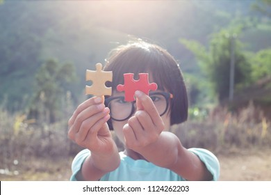 Little child holding piece of blank jigsaw puzzle