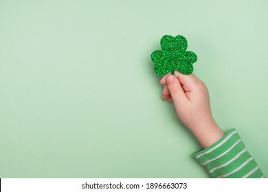 Little child holding shiny green Clover. St Patricks Day. Top view, flat lay, copy space