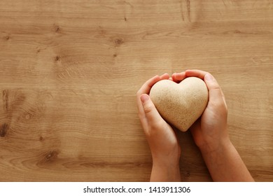 little child holding a wooden heart. father's and mother's day, love, hope and religion concept.