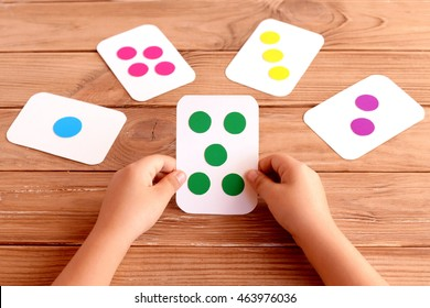 Little child holds a training card in his hands and learning the color, shape, quantity. Colorful flash cards for fun teaching kids. Early development concept. Wooden background