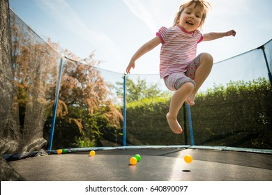 Little child jumping on big trampoline - outdoor in backyard