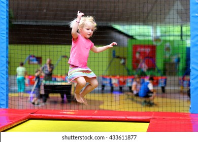 Little child jumping at trampoline in indoors playground. Active toddler girl having fun at sport center