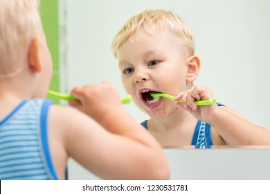 Little child kid boy brushing teeth in front of a mirror in bathroom