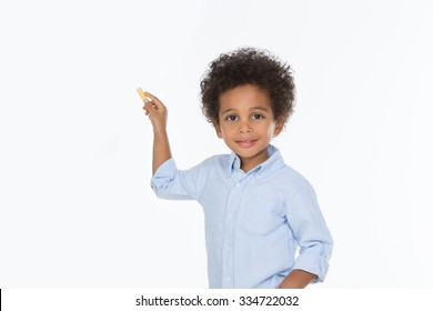 little child looking at the camera holding a yellow chalk