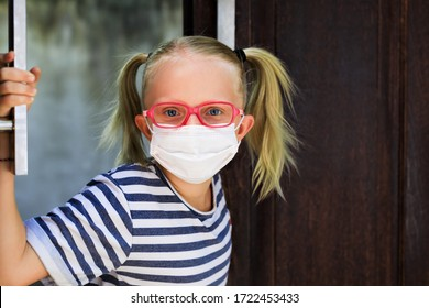 Little child looking out opened door after staying at home due banned street activity. Kid wearing medical face masks go out for outside walk. Ending coronavirus Covid-19 disease quarantine.