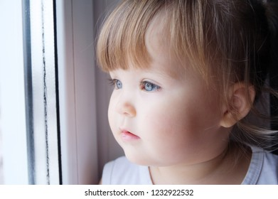 little child looking out window. baby girl longing to walk outdoors at rainy weather.